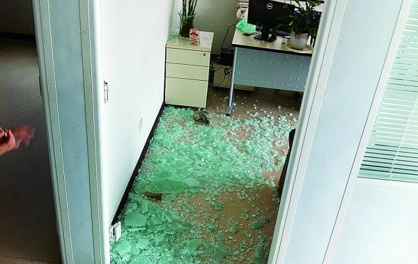 璃门自爆后碎玻璃满地 。